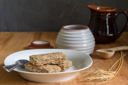 Wheat cereal bars dry in breakfast plate on wooden table with wheat ears in foreground and honey and milk jar in background