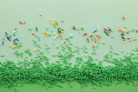 Green sprinkles on two tone green background with multi coloured sprinkles scattered - Green sprinkle background with space for text Stock Photo