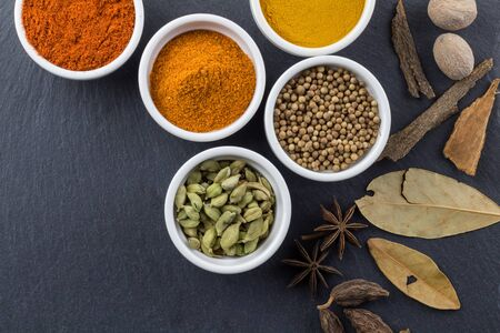 Spices in little white bowls on black slate background - Indian spice top view photo with space for text