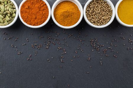 Indian spices in little white bowls on black background - top view photo Stock Photo