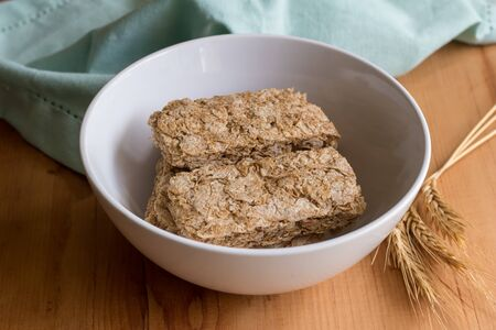 Wheat cereal in bowl with wheat spears on wooden table
