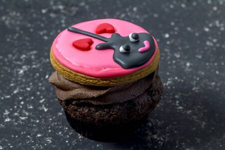 Valentines day cupcake isolated on black mottled background - fun cupcake with black guitar and two hearts with pink icing decorated on chocolate Standard-Bild - 128891857