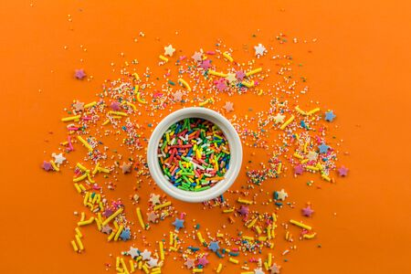 Sprinkles on bright orange background with little white bowl in middle of background and multi-colored sprinkles sprayed around Standard-Bild - 128891858