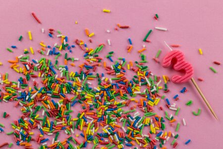 Birthday background with multi-colored cake topping sprinkles and number 3 birthday candle on pink background - top view Standard-Bild - 128891866