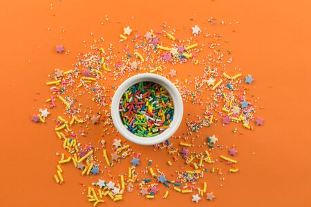 Sprinkles on orange background with single little white bowl with multi-colored sprinkles in centre - top view Standard-Bild - 128891874