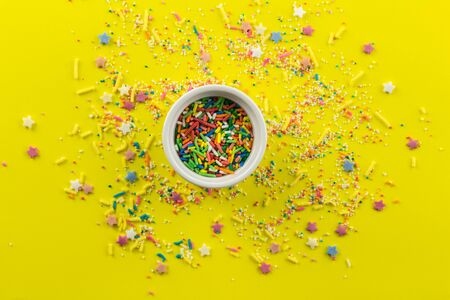 Sprinkles on yellow background with single little white bowl with multi-colored sprinkles and star shapes in centre - top view Standard-Bild - 128891872