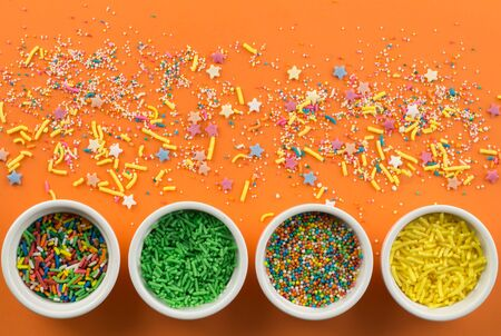 Sprinkles on bright orange background with little white bowls with various type of coloured sprinkles at bottom  and multi-colored cake topping sprinkles and star shapes sprayed around Standard-Bild - 128891875