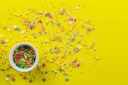 Sprinkles on bright yellow background with little white bowl with various type of coloured sprinkles at bottom  and multi-colored cake topping sprinkles and star shapes sprayed around