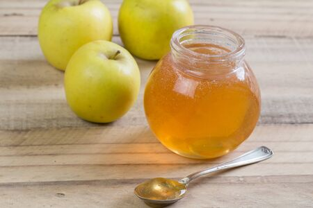 Apple jelly in a jar and apples on wooden background
