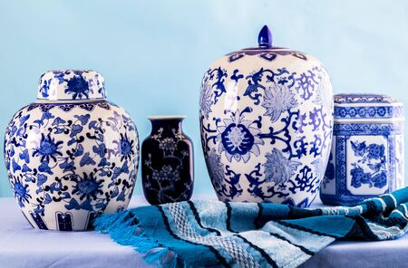 Still life with Japanese blue and white ginger jars and vases on blue against blue background - side view photo Stock Photo