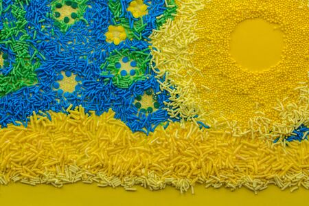 Abstract cake topping sprinkle background with conceptual picture consisting of yellow, blue and green sprinkles close up Standard-Bild - 128900619