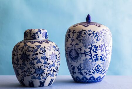 Still life with two blue and white ceramic ginger jars isolated on blue - side view with selective focus