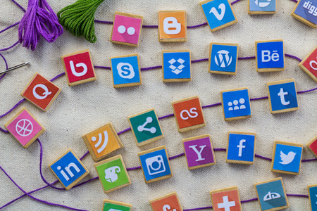 QUEENSTOWN, SOUTH AFRICA - 7 JULY 2019 -Social media background with social media logos on wooden game blocks joined with embroidery thread and needle on white linen background - Social networking concept Editorial