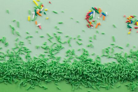 Green sprinkles on two tone green background with multi coloured sprinkles scattered - Green sprinkle background with space for text Stock fotó