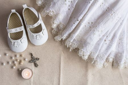 Christening background with baptism dress, shoes, candles and crystal cross pendant on white linen cloth