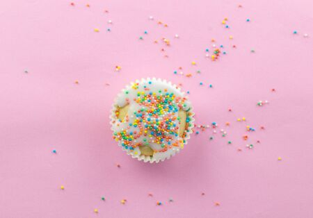 Little frosted white cupcake in centre of pink background sprinkled with multi - coloured round sprinkles on pink with copy space - top viiew photo Stock fotó