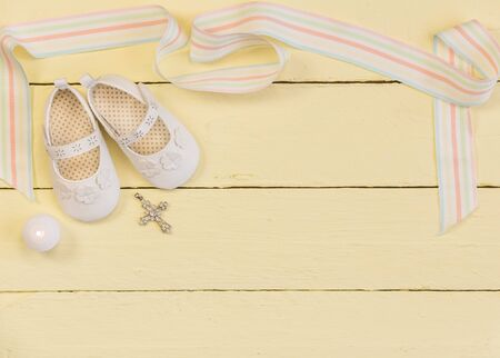 Christening background with white shoes,ribbon, candle and crystal cross pendant on pale yellow painted wooden background - top view photo 免版税图像