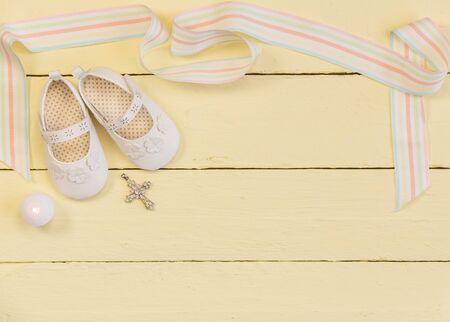 Taufhintergrund mit weißen Schuhen, Band, Kerze und Kristallkreuzanhänger auf hellgelb lackiertem Holzhintergrund - Foto von oben
