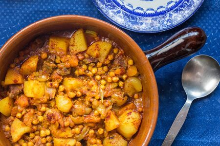 Chick pea, vegetables and meat curry in earthern ware casserole dish - top view photo