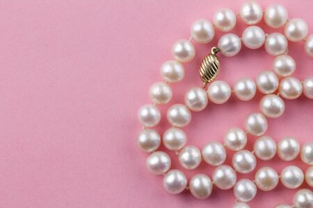 Pearl necklace with gold clasp on pink background - top view