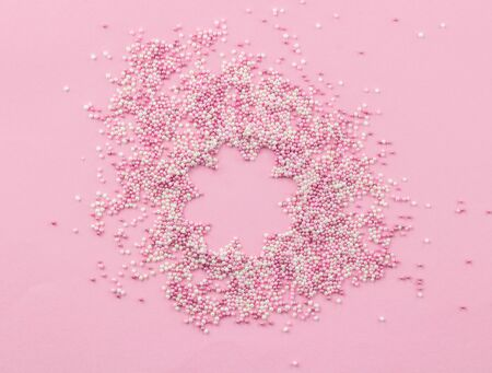 Pink and white edible pearlized sprinkles on pink background - Cake topping pearly pink with flower shape copy space in centre sprinkles top view photo