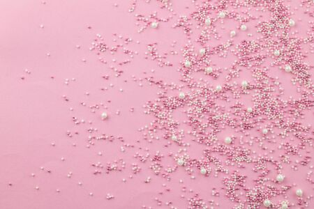 Pink and white edible pearlized sprinkles on pink background - Cake topping pearly pink sprinkles top view photo with copy space