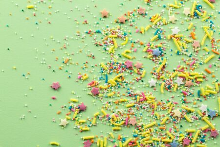Sprinkles on light green background - Assorted colourful cake topping sprinkles sprayed on green on bottom corner with space for text - top view of star shapes, dots and oblong sprinkles
