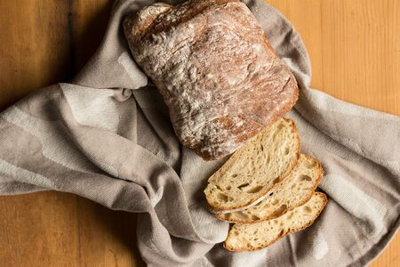 Whole sourdough bread loaf on kitchen cloth on rustic wooden table - Overhead photograph
