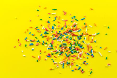 Multi-coloured sprinkles on bright yellow background - top view