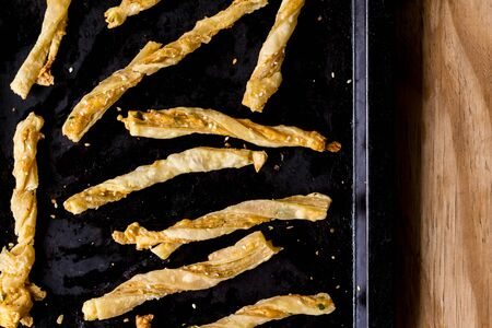 Cheesy cheese pastry straws with sesame seeds and bits of chili in oven pan  - top view photo Stock fotó