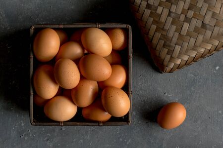 Eggs raw and whole in shells in square leaf basket with lid on side on dark grey texture background - top view photo