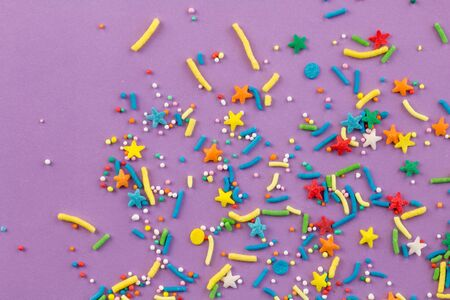 Sprinkle background with rainbow sprinkle shapes, stars, stripes, little balls on lilac background, close up top view photo Stock fotó