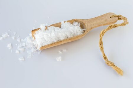 Salt flakes in wooden scoop isolated on white background - side view