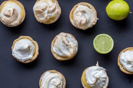 Lemon meringue tarts on black background - top view photo of limes and lime meringues