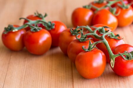 Cherry tomatoes isolated on wooden background - side view photo with selective focus