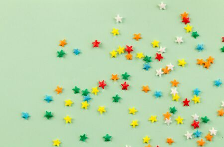 Sprinkle background with bright colourful star sprinkles scattered on pale green background with space for text