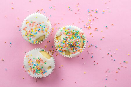 Three little white frosted white cupcakes in centre of pink background sprinkled with multi - coloured sprinkles on pink with copy space