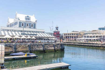 CAPE TOWN , SOUTH AFRICA - 01 JANUARY 2020: Side view of the Old Port Captain's building built in 1904 in with the red old clock tower and restaurants at the V & A Waterfront Cape Town a popular tourist attraction on New Years Day 2020