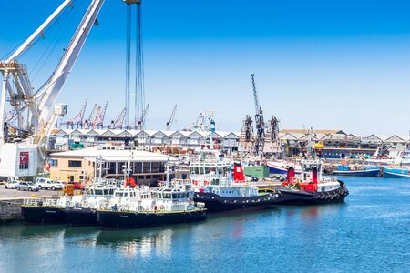CAPE TOWN , SOUTH AFRICA - 01 JANUARY 2020: Tugboats and harbour crane at the V & A Waterfront in Cape Town Harbour