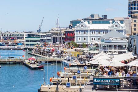 CAPE TOWN , SOUTH AFRICA - 01 JANUARY 2020: V & A Waterfront with many tourists celebrating a summer New Years day at the Cape Town harbour with Old Port Captain's building buildt in 1902 in background