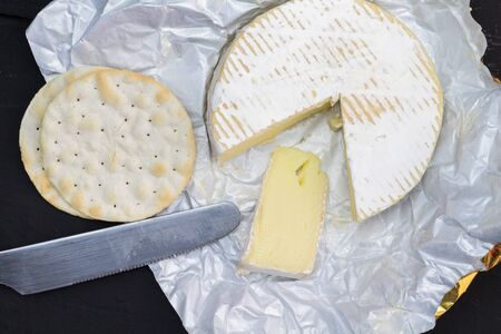 Camembert cheese whole with slice next to water crackers and knife - overhead photo 写真素材