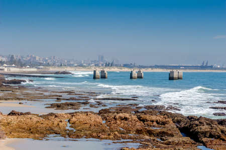 Old pier at Humewood Beach in Port Elizabeth with city buildings in background