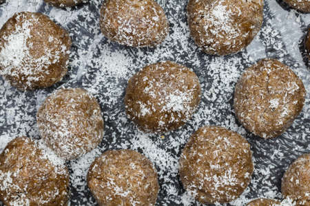 Date balls close up with coconut sprinkles - top view photo of traditional sweet date snack