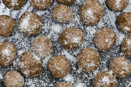 Many date balls close up with coconut sprinkles - top view photo of traditional sweet date snack