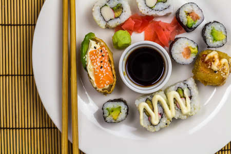 Sushi platter with assorted sushi rolls with chopsticks, ginger and wasabi - top view with copy space Banque d'images