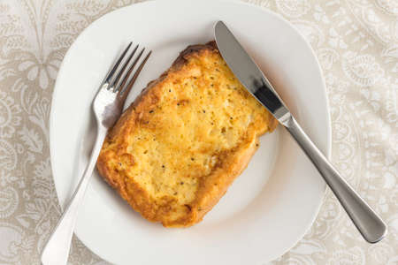 French toast with pepper and herbs - top view image with knife and fork