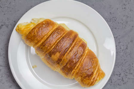 Croissant on white plate with copy space - top view close up image