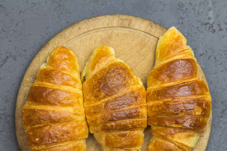Three croissants on a wooden board - top view image close up