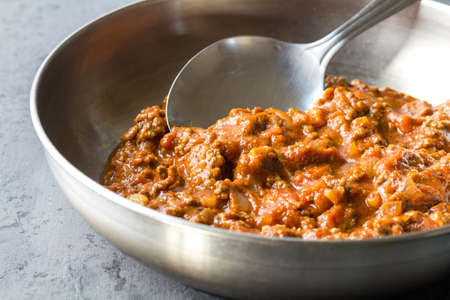 Bolognese (also know as Bolognesa or Bolonhesa) sauce in a pan with ladle on grey background with copy space - studio photo
