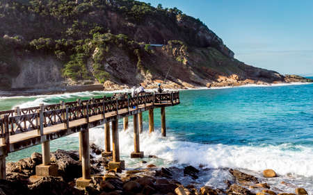 Pier at beach - pier with fishermen at Victoria Bay in Western Cape South Africa - popular surfing beach for surfers all over the country.